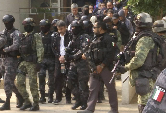 FILE - In this May 2, 2017 file photo, Damaso Lopez, a leader in Mexico's Sinaloa drug cartel, is escorted by police after his capture at an upscale apartment building in Mexico City. Lopez testified Wednesday, Jan. 23, 2019, at the U.S. trial of the Mexican drug lord known as El Chapo, implicating the kingpin's wife in his 2015 prison escape. (AP Photo/Jorge Barrera, File)