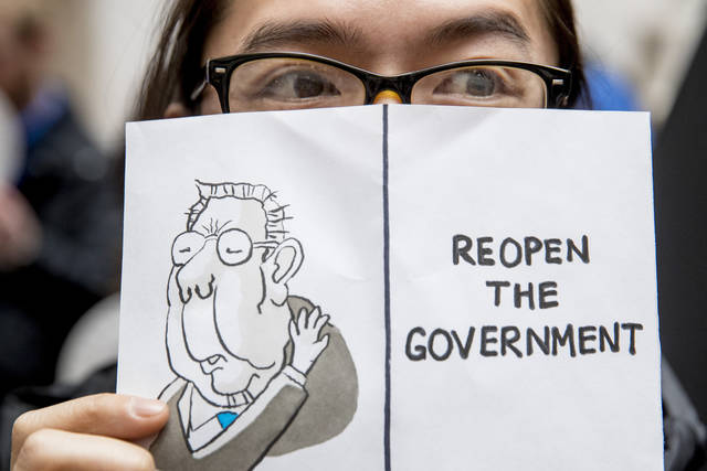 "A furloughed government worker affected by the shutdown holds a sign that reads ""Reopen the Government"" during a silent protest against the ongoing partial government shutdown on Capitol Hill in Washington, Wednesday, Jan. 23, 2019. (AP Photo/Andrew Harnik)"