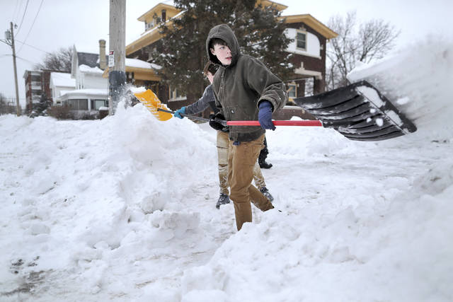 Nathan Tearman, front center, gets help from his brother James as they shovel the driveway of their home on Monday, Jan. 28, 2019, after a winter snowstorm made its way through Janesville, Wis. Democratic Wisconsin Gov. Tony Evers declared a state of emergency shortly after noon Monday, citing the snow and severe cold that is forecast for the days ahead. (Anthony Wahl/The Janesville Gazette via AP)