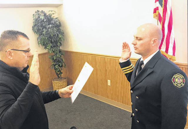 Genoa Township Fiscal Officer Patrick Myers swears in new Fire Marshal Anthony Caito.