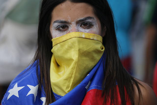 An anti-government protester covers her face with a Venezuelan flag, and uses toothpaste around her eyes to help lessen the effect of tear gas, during clashes with security forces after a rally demanding the resignation of President Nicolas Maduro in Caracas, Venezuela, Wednesday, Jan. 23, 2019. The head of Venezuela's opposition-run congress declared himself interim president at the rally, until new elections can be called. (AP Photo/Fernando Llano)