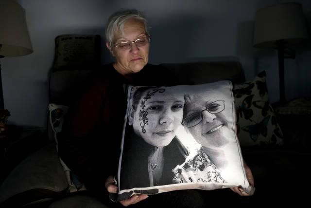 In a photo taken Friday, Jan. 18, 2019, Deborah Fuller poses for a photograph for The Associated Press with a pillow showing a photo of her late daughter, Sarah Fuller, left, who passed of a prescription drug overdose, and her during an interview in her home in West Berlin, N.J. The trial of a Insys Therapeutics Inc. founder John Kapoor, who accused of scheming to bribe doctors into prescribing a powerful painkiller, is putting a spotlight on the nation's deadly opioid crisis. (AP Photo/Julio Cortez)