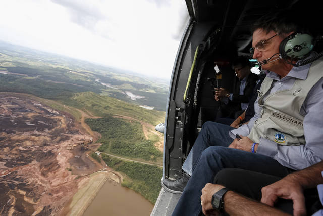 In this handout photo released by Brazil's Government Press Office, Brazil's President Jair Bolsonaro surveys an area buried by mud, in Brumadinho, Brazil, Saturday, Jan. 26, 2019. Rescuers in helicopter on Saturday searched for survivors in a huge area in southeastern Brazil buried by mud from the collapse of dam holding back mine waste, with at least nine people dead and up to 300 missing. (Isac Nobrega/Brazil's Government Press Office via AP)