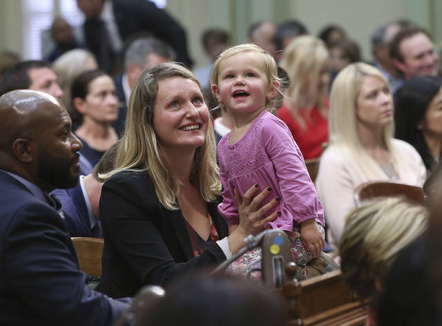 FILE - In this Monday, Dec. 3, 2018, file photo, freshman Assemblywoman Buffy Wicks, a Democrat, and her daughter, Josephine, 2, look at the Assembly Gallery during the Legislative session in Sacramento, Calif. State legislatures across the country are convening this year with at least 17 new women in top leadership roles, after a record-setting election for female candidates. Wicks won her seat in November. (AP Photo/Rich Pedroncelli, File)