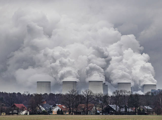 FILE---In this  Jan.6, 2019 file photo water vapour rises from the cooling towers of the Joenschwalde lignite-fired power plant of Lausitz Energie Bergbau AG (LEAG) in Brandenburg, Germany. (Patrick Pleul/dpa via AP)