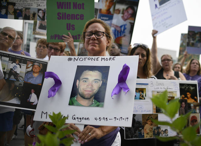 Christine Gagnon, of Southington, Conn., holds a sign during a protest with others who have lost loved ones to OxyContin and Opioid overdoses at the Purdue Pharma headquarters in Stamford, Conn., on Friday, Aug. 17, 2018. Gagnon lost her son Michael 13 months earlier. (AP Photo/Jessica Hill)