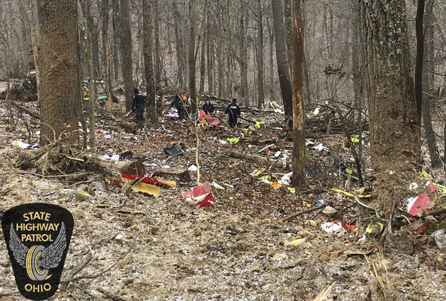 In this photo provided by the Ohio State Highway Patrol, authorities survey the scene of wreckage where a medical helicopter crashed in a remote wooded area in Brown Township, Ohio, on its way to pick up a patient, Tuesday, Jan. 29, 2019. There had been no reports of anyone else injured in the crash. No names were released immediately. A few crew members were all killed in the crash, authorities said. (Ohio State Highway Patrol via AP)