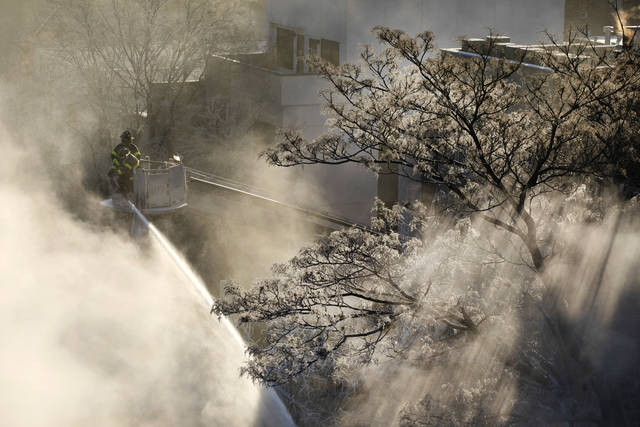 Ice forms on tree branches as New York firefighters battle a blaze in a commercial building in the Bedford Stuyvesant neighborhood of Brooklyn, Thursday, Jan. 31, 2019 in New York. Firefighters around New York state have been grappling with brutal cold during big blazes. (AP Photo/Mark Lennihan)