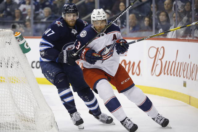 Winnipeg Jets' Adam Lowry (17) chases Columbus Blue Jackets' Seth Jones (3) around the net during the second period of an NHL hockey game Thursday, Jan. 31, 2019, in Winnipeg, Manitoba. (John Woods/The Canadian Press via AP)