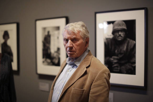 Veteran British conflict photographer Don McCullin poses for photographers at the launch of his retrospective exhibition at the Tate Britain gallery in London, Monday, Feb. 4, 2019. The exhibition includes over 250 of his black and white photographs, including conflict images from the Vietnam war, Northern Ireland, Cyprus, Lebanon and Biafra, alongside landscape and still life images. (AP Photo/Matt Dunham)
