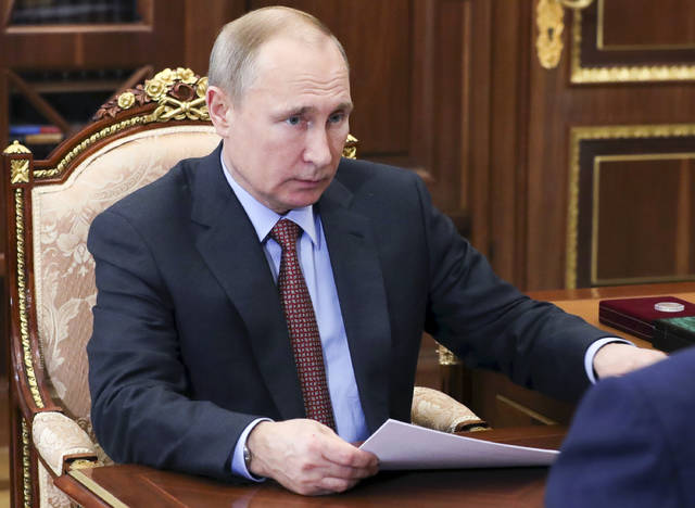 Russian President Vladimir Putin listens to Russian Roscosmos head Dmitry Rogozin during a meeting in the Kremlin in Moscow, Russia, Monday, Feb. 4, 2019. Rogozin reported that Roscosmos plans to double the number of space launches this year compared to 2018. (Mikhail Klimentyev, Sputnik, Kremlin Pool Photo via AP)
