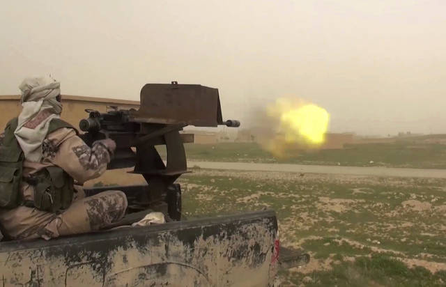 This frame grab from video posted online Jan. 18, 2019, by supporters of the Islamic State group, purports to show a gun-mounted IS vehicle firing at members of the U.S.-backed Syrian Democratic Forces, in the eastern Syrian province of Deir el-Zour, Syria. As they cling to the tiny remains of what was once a self-styled caliphate spanning two countries, IS militants are laying the groundwork for an insurgency. Activists say they are carrying out targeted assassinations, setting up flying checkpoints and distributing fliers to intimidate residents. They fear the group could stage an even bigger comeback if U.S. forces withdraw from Syria. (Militant Photo via AP)