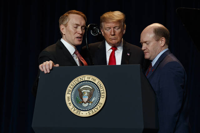 Rep. James Lankford, R-Okla., left, President Donald Trump, center, and Sen. Chris Coons, D-Del., pray during the National Prayer Breakfast, Thursday, Feb. 7, 2019, in Washington. (AP Photo/ Evan Vucci)