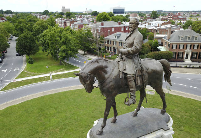 FILE - This June 27, 2017 file photo shows the statue of Confederate General Robert E. Lee in the middle of a traffic circle on Monument Avenue in Richmond, Va. Statues of Confederate generals and other symbols of Richmond's once-booming slave trade stand as painful reminders of the city's turbulent racial past. (AP Photo/Steve Helber)
