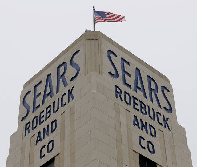 FILE- In this Jan. 8, 2019, file photo an American flag flies above a Sears store in Hackensack, N.J. A bankruptcy judge has blessed a $5.2 billion plan by Sears chairman and biggest shareholder Eddie Lampert to keep the iconic business going. The approval means roughly 425 stores and 45,000 jobs will be preserved. (AP Photo/Seth Wenig, File)