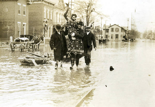 FILE - In this 1913 file photo, rescuers carry a woman from the 1913 Dayton floodwaters in Dayton, Ohio.  A new opera revisits the Great Flood of 1913, a Midwestern disaster that killed hundreds, left thousands homeless, and destroyed countless bridges and businesses, but that also paved the way for flood control innovations. The dark subject matter is well-suited to opera, said Peggy Kriha Dye, general and artistic director of Opera Columbus. (Dayton Daily News via AP, File)