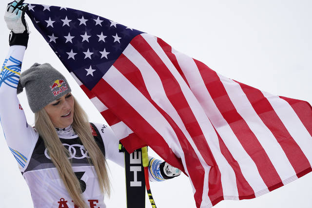 Third placed United States' Lindsey Vonn celebrates on the podium after the women's downhill race, at the alpine ski World Championships in Are, Sweden, Sunday, Feb. 10, 2019. (AP Photo/Giovanni Auletta)