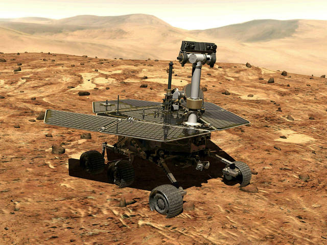 FILE - This illustration made available by NASA shows the rover Opportunity on the surface of Mars. The exploratory vehicle landed on Jan. 24, 2004, and logged more than 28 miles (45 kilometers) before falling silent during a global dust storm in June 2018. There was so much dust in the Martian atmosphere that sunlight could not reach Opportunity's solar panels for power generation. (NASA via AP)