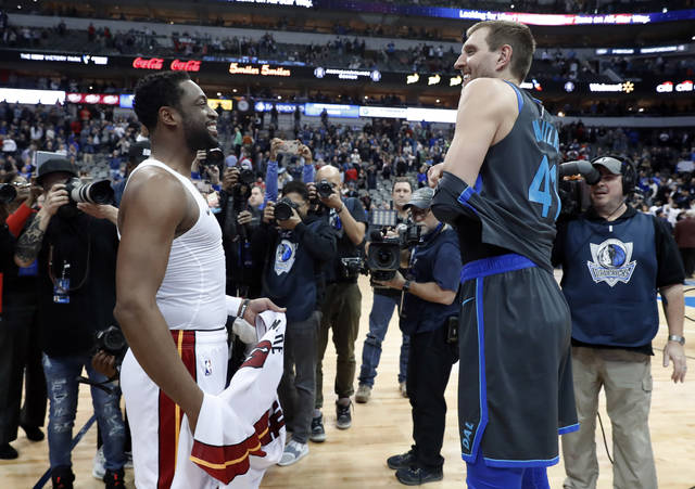 Miami Heat's Dwyane Wade, left, and Dallas Mavericks' Dirk Nowitzki, right, talk as they swap jerseys after an NBA basketball game in Dallas, Wednesday, Feb. 13, 2019. (AP Photo/Tony Gutierrez)