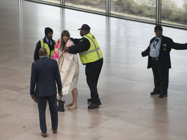 National Gallery of Art security cover Radical Matriarchy member Laura Newman with a blanket after she removed her clothes and sang during a protest in the museum, Thursday, Feb. 14, 2019 in Washington. Radical Matriarchy was protesting the fact that 90% of the art inside is by white men. In the nation's capital, it can be hard for protesters to stand out. Fifty people _ or even 500 _ holding signs and shouting hardly merits a second glance in this city of protests. That's why Washington activists have to get creative. (AP Photo/Kevin Wolf)