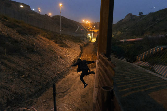 FILE - In this Dec. 21, 2018, file photo, a Honduran youth jumps from the U.S. border fence in Tijuana, Mexico.   California's attorney general filed a lawsuit Monday, Feb. 18, 2019, against President Donald Trump's emergency declaration to fund a wall on the U.S.-Mexico border. Xavier Becerra released a statement Monday saying 16 states — including California — allege the Trump administration's action violates the Constitution. (AP Photo/Daniel Ochoa de Olza, File)