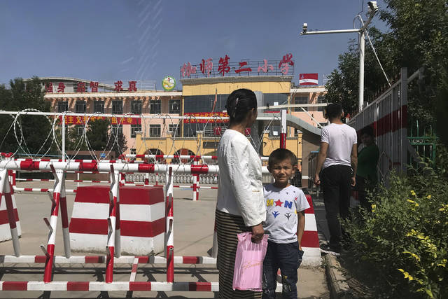 FILE - In this Aug. 31, 2018, file photo, a child and a woman wait outside a school entrance mounted with surveillance cameras and barricades with multiple layers of barbed wire in Peyzawat, western China's Xinjiang region. The Chinese database Victor Gevers found online was not just a collection of old personal details. The discovery by Gevers, a Dutch cybersecurity researcher who revealed it on Twitter last week, has given a rare glimpse into China's extensive surveillance of Xinjiang, a remote region home to an ethnic minority population that is largely Muslim. The area has been blanketed with police checkpoints and security cameras that apparently are doing more than just recording what happens. The database Gevers found appears to have been recording people's movements tracked by facial recognition technology, he said, logging more than 6.7 million coordinates in a span of 24 hours. (AP Photo/Ng Han Guan, File)