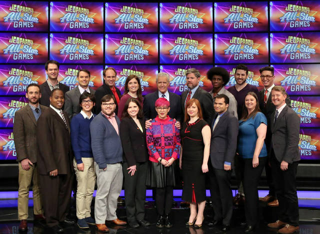 "This image released by Jeopardy Productions, Inc. shows, front row from left, Brad Rutter, Colby Burnett, Alan Lin, Seth Wilson, Larissa Kelly, Monica Thieu, Pam Mueller, Matt Jackson, Jennifer Giles and Ken Jennings, back row from left, Ben Ingram,  Roger Craig, David Madden, Julia Collins, host Alex Trebek, Austin Rogers, Leonard Cooper, Alex Jacob and Buzzy Cohen on the set of the game show ""Jeopardy!""  The game show's first-ever team tournament will pit groups of former champions against each other in 10 weekday episodes airing from Wednesday, Feb. 20, to Tuesday, March 5. (Jeopardy Productions, Inc. via AP)"
