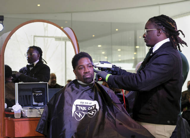 "In this Sunday, Feb. 17, 2019 photo, Yusuf Lateef receives a haircut from Andre ""Drizzy the Barber"" Johnson, during ""The Art of the Cut"" event at Toledo Museum of Art's GlasSalon in Toledo, Ohio. ""The Art of the Cut"" featured live demonstrations from barbers affiliated with a ProMedica initiative that partners with predominantly black barbershops to provide health screenings and education there. (Jetta Fraser/The Blade via AP)"