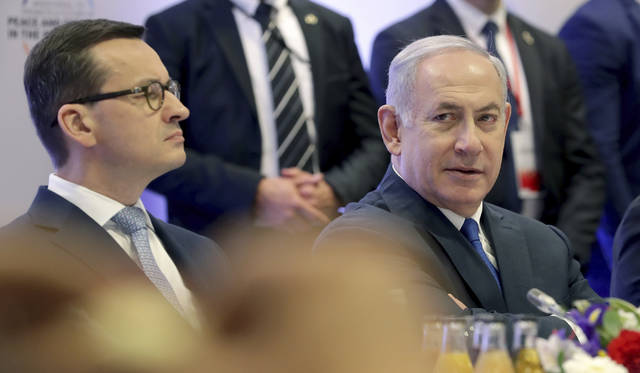 """File -- In this Thursday, Feb. 14, 2019 photo Poland's Prime Minister Mateusz Morawiecki, left, and Israeli Prime Minister Benjamin Netanyahu, right, attend a meeting in Warsaw, Poland. Poland's prime minister canceled plans for his country to send a delegation to meeting in Jerusalem on Monday after the acting Israeli foreign minister Israel Katz said that Poles """"collaborated with the Nazis"""" and """"sucked anti-Semitism from their mothers' milk"""". (AP Photo/Michael Sohn)"""