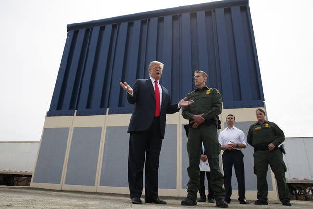 FILE - In this March 13, 2018, file photo, President Donald Trump talks with reporters as he reviews border wall prototypes in San Diego. Disputes over Trump's border wall and California's bullet train have become mixed together as the feud between the White House and the nation's most populous state intensifies. The Trump administration said on Tuesday, Feb. 19, 2019, it plans to cancel or claw back $3.5 billion in federal dollars allocated to California's high-speed rail project. (AP Photo/Evan Vucci, File)