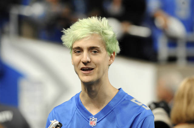 "File-This Sept. 10, 2018, file photo shows Tyler ""Ninja"" Blevins before an NFL football game between the Detroit Lions and New York Jets in Detroit. For the first time since its meteoric rise, ""Fortnite"" is no longer a no-doubt victory royale atop the video game industry. ""Apex Legends"",  a battle royale from Electronic Arts, has stormed the market and smashed ""Fortnite"" records for downloads and viewership since its release three weeks ago. Blevins and other streaming stars have powered that surge, as has the emergence of an 18-year-old ""Apex"" superstar. Esports teams are already scrambling to sign talented players and invest long-term in the breakout title.  (AP Photo/Jose Juarez, File)"