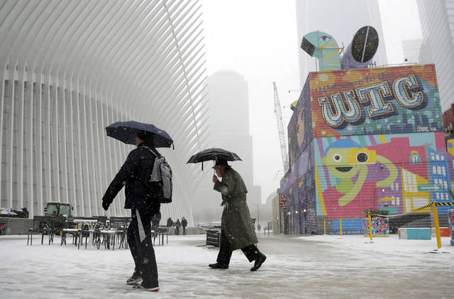Pedestrians hold umbrellas while walking under light snow near the Oculus in lower Manhattan, Wednesday, Feb. 20, 2019, near The Oculus transportation hub in New York. (AP Photo/Julio Cortez)