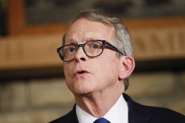 In this Jan. 14, 2019 file photo Mike DeWine speaks before being sworn-in as the 70th Governor of Ohio alongside his wife Fran, center right in Cedarville, Ohio. DeWine's administration on Thursday, Feb. 21, 2019 recommended increasing the state gas tax by 18 cents a gallon beginning July 1 and annually adjusting that tax for inflation to provide sufficient funding for maintenance of roads and bridges. (AP Photo/John Minchillo, Pool, file)