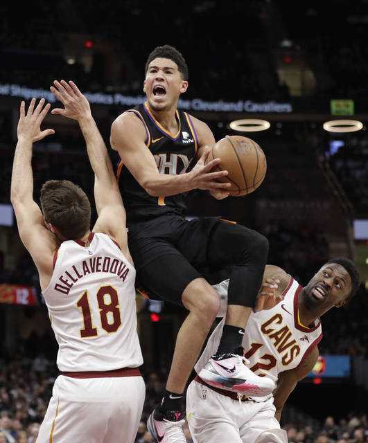 Phoenix Suns' Devin Booker, center, drives to the basket between Cleveland Cavaliers' Matthew Dellavedova, left, and David Nwaba in the second half of an NBA basketball game, Thursday, Feb. 21, 2019, in Cleveland. (AP Photo/Tony Dejak)