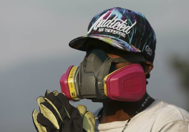 An anti-government Venezuelan migrant wearing protective gear rests from confrontations with Venezuelan National Guards who are blocking the Simon Bolivar International Bridge, in La Parada near Cucuta, Colombia, Sunday, Feb. 24, 2019, on the border with Venezuela. A U.S.-backed drive to deliver foreign aid to Venezuela on Saturday met strong resistance as troops loyal to President Nicolas Maduro blocked the convoys at the border and fired tear gas on protesters. (AP Photo/Fernando Vergara)