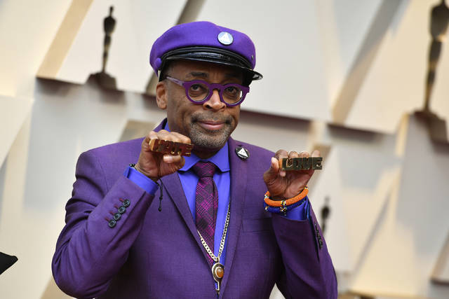 "Spike Lee holds up brass knuckles reading ""hate"" and ""love"" from his iconic film ""Do The Right Thing"" as he arrives at the Oscars on Sunday, Feb. 24, 2019, at the Dolby Theatre in Los Angeles. (Photo by Jordan Strauss/Invision/AP)"
