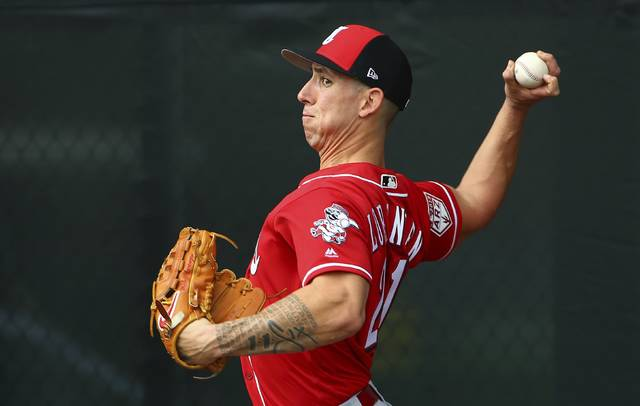 FILe - In this Feb. 13, 2019, file photo, Cincinnati Reds pitcher Michael Lorenzen throws a pitch during workouts at the Reds spring training baseball facility, in Goodyear, Ariz. With Billy Hamilton gone, the Reds have to decide who will play center field. They've got an assortment of candidates, including reliever Michael Lorenzen. (AP Photo/Ross D. Franklin, File)