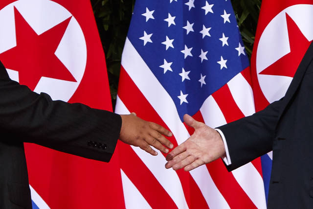 FILE - In this June 12, 2018, file photo, U.S. President Donald Trump, right, reaches to shake hands with North Korea leader Kim Jong Un at the Capella resort on Sentosa Island in Singapore. (AP Photo/Evan Vucci, File)