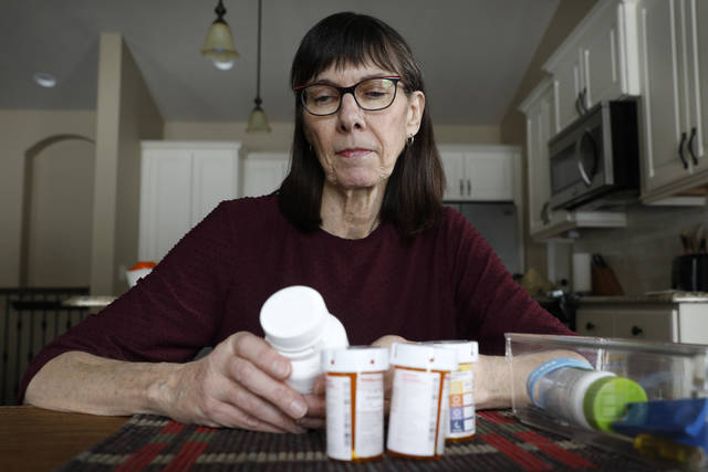 Retired public school teacher Gail Orcutt, of Altoona, Iowa, looks over some of the prescription drugs she takes, Friday, Feb. 15, 2019, in Altoona, Iowa. Orcutt pays $2,600 the first month of the year, and then $750 every other month for a lung cancer medication. With health care a top issue for American voters, Congress may actually be moving toward doing something this year to address the high cost of prescription drugs. (AP Photo/Charlie Neibergall)