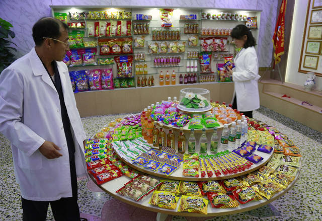 FILE - In this Oct. 22, 2018, file photo, Kwon Yong Chol, left, the chief engineer at the Songdowon General Foodstuffs Factory, shows samples of products at his facility in Wonsan, North Korea. With U.S. President Donald Trump and North Korean leader Kim Jong Un descending on Hanoi for their second summit, there has been a persistent suggestion that Kim will look around at the relative prosperity of his Vietnamese hosts - who are certainly no strangers to U.S. hostility - and think that he, too, should open up his country to more foreign investment and trade. (AP Photo/Dita Alangkara, File)