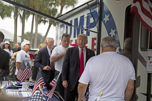 In an Aug. 24, 2016 photo, Republican presidential nominee Donald Trump meets supporters organizing voter registration and support for his campaign just before a rally at the Florida State Fairgrounds in Tampa, Fla. A woman is alleging in a new lawsuit filed Monday, Feb. 25, 2019, that Inside the RV seen here, Trump kissed a member of his campaign staff without consent. The woman, Alva Johnson, can be seen in the background of this photo wearing a Trump shirt and a hat on the left side of the frame.(Loren Elliott/Tampa Bay Times via AP)