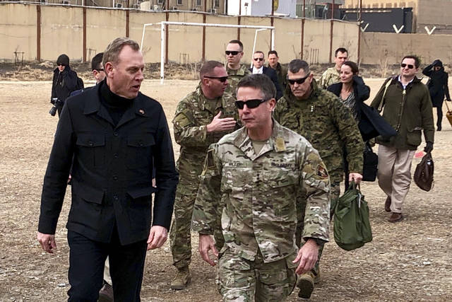 FILE - In this Feb. 11, 2019, photo, acting Defense Secretary Patrick Shanahan, left, arrives in Kabul, Afghanistan to consult with Army Gen. Scott Miller, right, commander of U.S. and coalition forces, and senior Afghan government leaders. Shanahan, the former Boeing executive, was in a familiar place, aboard an airplane, when he got word of a bolt-from-the-blue political shot across his bow. A key senator seemed to have buried Shanahan's chances of being nominated as the next secretary of defense. The crisis passed, but it highlighted the precarious position Shanahan occupies as he waits for President Donald Trump to decide who he will successor to Jim Mattis as leader of the Pentagon. (AP Photo/Robert Burns)
