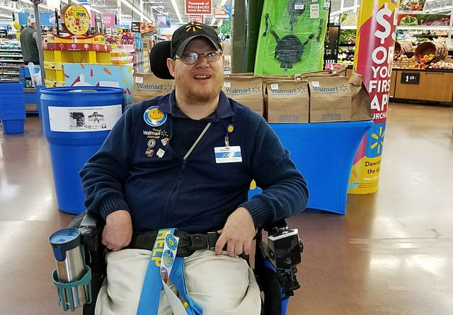 In this April 21, 2018 photo provided by Rachel Wasser, Walmart greeter John Combs works at a Walmart store in Vancouver, Wash. Combs, who has cerebral palsy, and other greeters with disabilities are threatened with job loss as Walmart transforms the greeter position into one that's more physically demanding. Combs was devastated and then angered by his impending job loss. (Rachel Wasser via AP)
