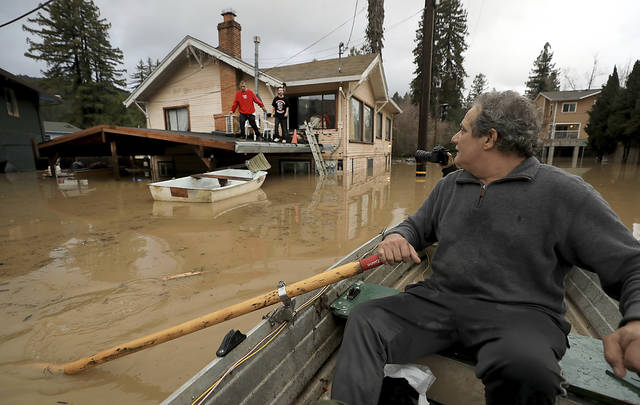 "Jonathan Von Renner checks on his son Jonathan Jr., and friend Emilio Ontivares in lower Guerneville, Calif., Wednesday, Feb. 27, 2019. Two Northern California communities are accessible only by boat after a rain-swollen river overflowed its banks following a relentless downpour. The Sonoma County Sheriff's Office says Guerneville, ""is officially an island"" and another nearby town was also isolated by floodwaters. (Kent Porter/The Press Democrat via AP)"