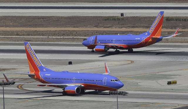 FILE - In this Sept. 4, 2013 file photo, a Southwest Airlines Boeing 737 takes off, rear, as another taxis in the north runway complex at Los Angeles International Airport (LAX). The airline says it has gained government approval to begin flights between California and Hawaii, capping a long effort that was delayed by the government shutdown. The airline's chief operating officer, Mike Van de Ven, told employees Wednesday, Feb. 27, 2019, that the Federal Aviation Administration granted the authorization. (AP Photo/Reed Saxon, File)