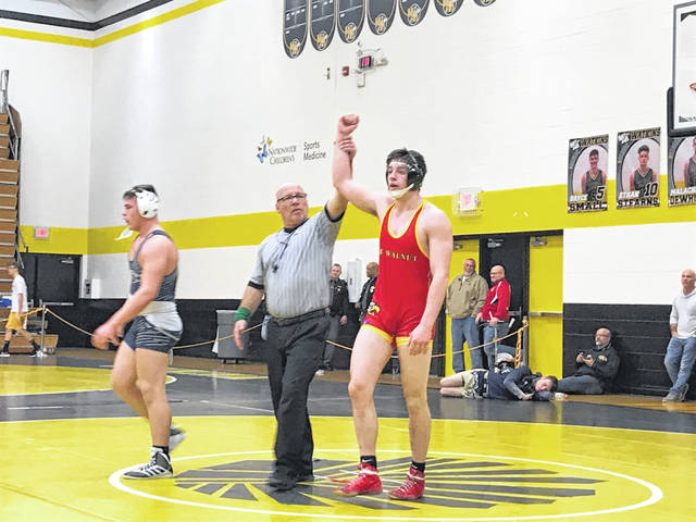 A Big Walnut wrestler gets his hand raised in victory.
