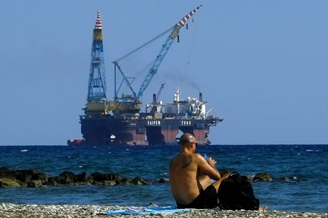 "FILE - In this Sunday, Oct. 15, 2017 file photo, a man sits on a beach as a drilling platform is seen in the background outside from Larnaca port, in the eastern Mediterranean island of Cyprus. Cyprus' energy minister says ExxonMobil has discovered the third-biggest gas deposit in the world in the last two years. Announcing the results on Thursday, Feb. 28, 2019, of exploratory drilling, Energy Minister Georgios Lakkotrypis said the ""world class"" discovery offers proof of the potential for more hydrocarbon discoveries in waters off the east Mediterranean island nation that could become an alternative energy source for Europe. (AP Photo/Petros Karadjias, File)"