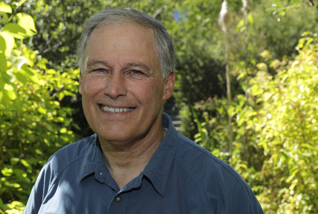 FILE - In this file photo taken July 23, 2018, Washington Gov. Jay Inslee poses for a photo on a path near his home on Bainbridge Island, Wash. Inslee is adding his name to the growing 2020 Democratic presidential field. The 68-year-old is announcing his bid Friday, March 1, 2019, in Seattle after recent travels to two of the four early-nominating states. (AP Photo/Ted S. Warren, File)