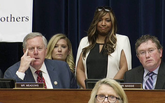 "In this image made from a Wednesday, Feb. 27, 2019, video, Rep. Mark Meadows, R-N.C., listens as he questions Michael Cohen, President Donald Trump's former lawyer, as Cohen testifies before the House Oversight and Reform Committee on Capitol Hill in Washington. Lynne Patton, who works in the Trump administration at the Department of Housing and Urban Development, stands behind Meadows, as Meadows said to Cohen, ""I asked Lynne to come today in her personal capacity to actually shed some light."" (AP Photo)"