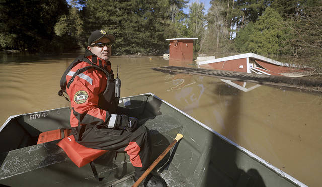John Buergler of the Sonoma County Sheriff's marine unit patrols Neely Road in Guerneville, Thursday, Feb. 28, 2019 as the Russian River recedes, but continues to flood. (Kent Porter/The Press Democrat via AP)